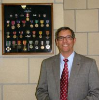 Rick Seitz with hid dads medals at Seitz Elementary